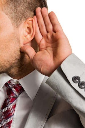 insider information: a man  holds his hand to his ear Stock Photo