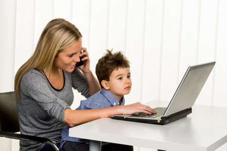 e work: mother and son on the computer, symbol of home, family and career, double burden Stock Photo