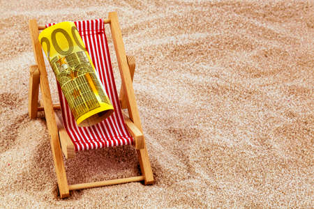 holiday profits: a deck chair with a euro banknote. photo icon for save on holiday and when traveling