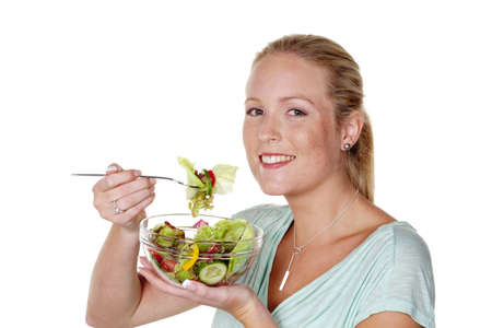 eat right: a young woman eating a crunchy salad at lunch time. healthy diet with vitamins.