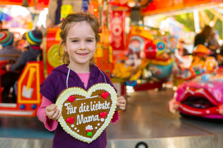 gingerbread heart: a little girl hold a heart made of gingerbread for the mother in her hand. representative photo mother