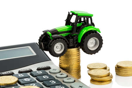 reckon: farmers in agriculture have to reckon with rising costs. higher prices for food, fertilizer and plants. tractor with coins and calculator
