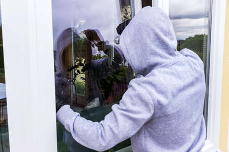 criminal act: a burglar trying to break in an open window with a crowbar