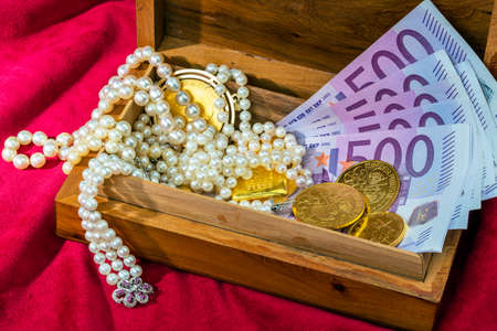 tangible: gold coins and bars with decorations on red velvet. photo icon for wealth, luxury, wealth tax.