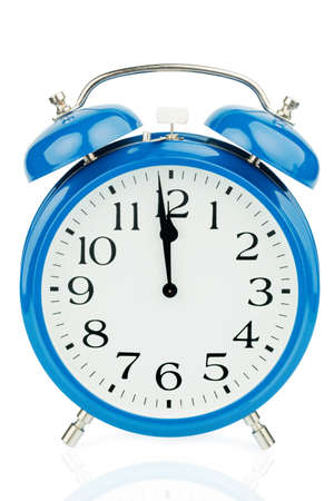 five to twelve: a blue alarm clock on white background. five to twelve Stock Photo