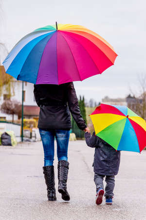 mother and child with umbrella, a symbol of solidarity, help, aid package, bailout, Stock Photo
