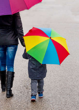 time deficit: mother and child with umbrella, a symbol of solidarity, help, aid package, bailout