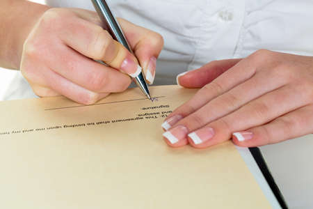 notieren: a woman signs a contract or a will with a fountain pen.