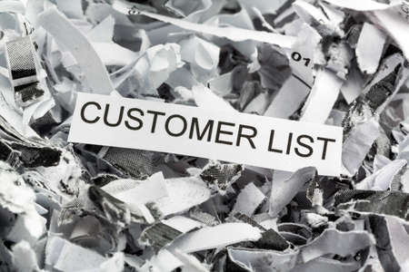 paper shredder: shredded paper tagged with customer list, symbolic photo for data destruction, data protection and customer data Stock Photo