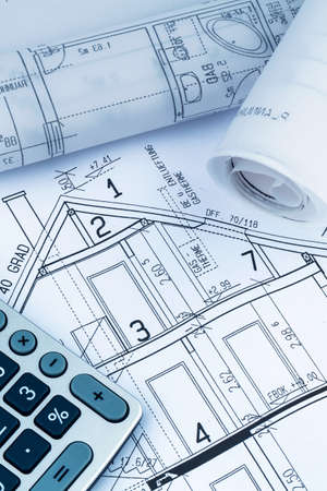 construction draftsman: an architects blueprint with a calculator. symbolic photo for funding and planning of a new home.