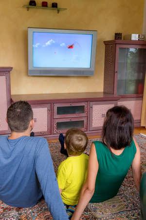 ver tv: la familia se sienta delante de un televisor y ver un programa para niños en. Foto de archivo