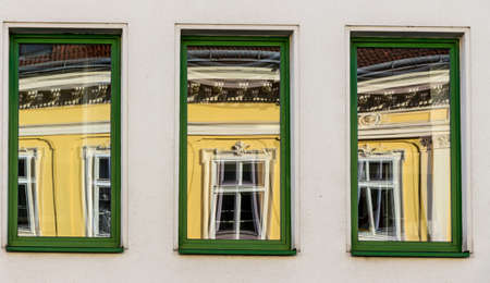 renovate old building facade: a renovated house reflected in modern windows of an office building