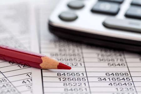 a calculator is on a balance sheet numbers are statistics. photo icon for sales, profits and costs. Archivio Fotografico