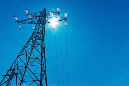torres de alta tension: las líneas de alta tensión poste de energía con el sol y el cielo azul. suministro de energía por línea eléctrica. Foto de archivo