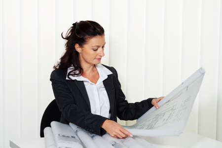 architect with blueprint in the office. a residential building plans are processed photo