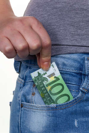 the hand of a young woman pulling a euro note from the pocket of her jeans photo