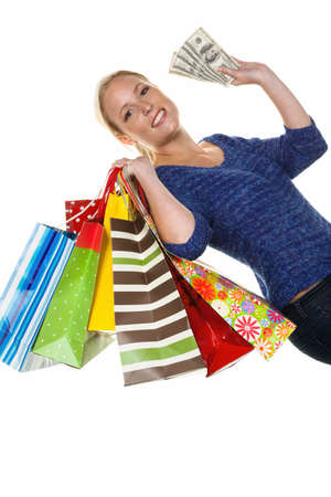 behave: a young woman with colorful shopping bags while shopping. with dollar banknotes