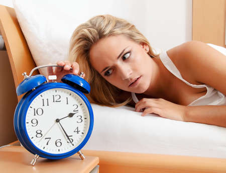 overtired: insomnia with clock at night. woman can not sleep.