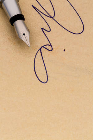 legacy: a signature and a fountain pen on yellow paper. symbolic photo for contract, testament and graphology