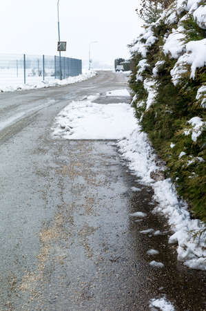 wetness: snow on sidewalk and street, symbol photo for accident risk and r�umpflicht