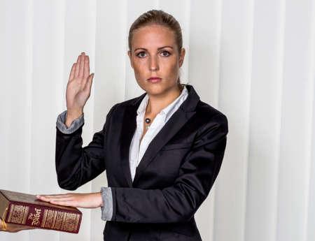 zegt een vrouw als getuige voor de rechtbank in een rechtszaak. wordt beëdigd en zweert op de bijbel. Stockfoto