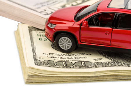 fcc: a car is on dollar bills. costs for the purchase of automobiles, gasoline, insurance and other car costs Stock Photo