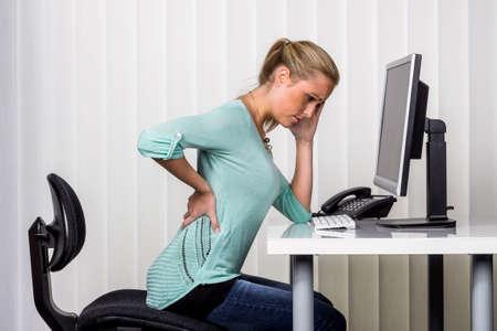eine Frau sitzen an einem Schreibtisch und hat Schmerzen im R�cken. Foto Symbol f�r die richtige Haltung bei der Arbeit im B�ro.