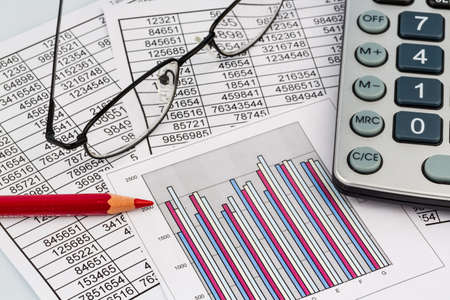 sheet: a calculator is on a balance sheet numbers are statistics. photo icon for sales, profits and costs. Stock Photo