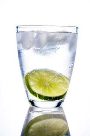 quencher: a glass of fresh drinking water and a lime. bottled water as a thirst quencher.
