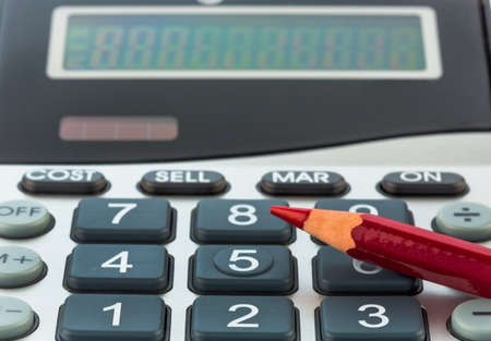 bad economy: a red pen is on a calculator. save on costs, expenses and budget for bad economy Stock Photo