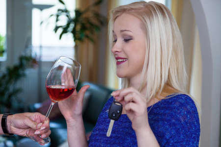 sobriety: a young woman with car key denied a glass of wine. do not drink and drive Stock Photo