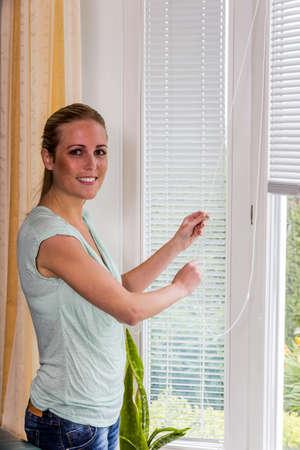 une femme laisse avec une fenêtre baisser les stores.
