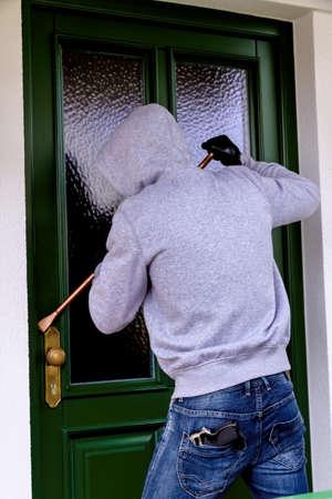lawbreaker: a burglar trying to break a door.