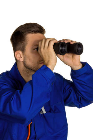 doldrums: a worker in an industrial enterprise with binoculars looking for jobs or jobs Stock Photo