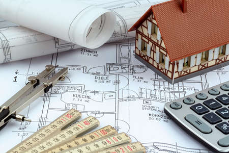 single familiy: an architects blueprint with a calculator. symbolic photo for funding and planning of a new home.
