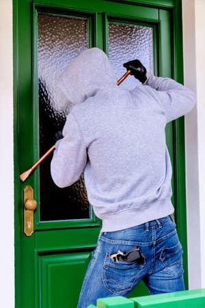 delito: un ladrón tratando de romper una puerta.