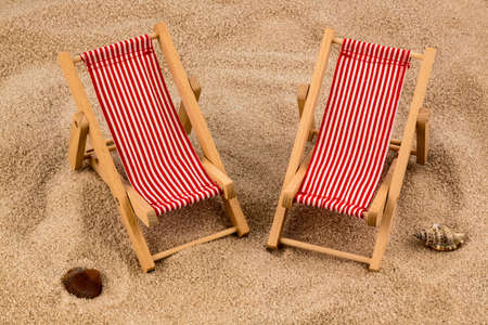 holiday profits: a small deck chair  on a sandy beach. symbolic photo for vacation, holiday, travel Stock Photo