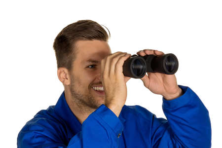 investigated: a worker in an industrial enterprise with binoculars looking for jobs or jobs Stock Photo