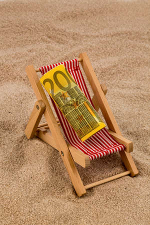 a deck chair with a euro banknote. photo icon for save on holiday and when traveling photo