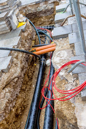 energy suppliers: at a construction site of new lines for water, heating, district heating and electricity are drawn. pit with supply lines Stock Photo
