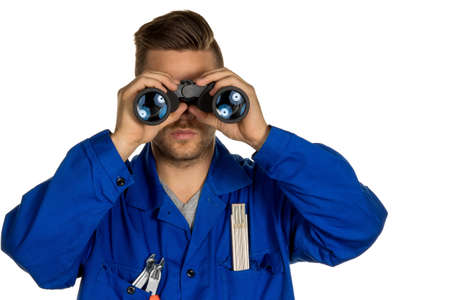 investigated: a worker in an industrial enterprise  with binoculars looking for jobs or jobs