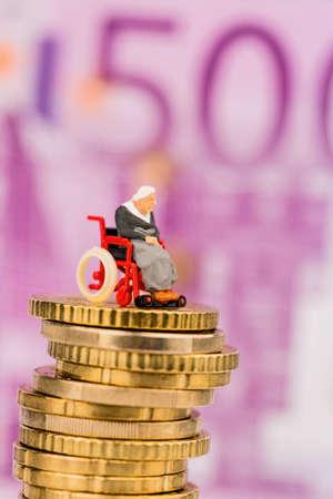 public health: mujer en silla de ruedas en la pila de dinero foto s�mbolo de la asignaci�n de asistencia discapacidad y costos de salud p�blica