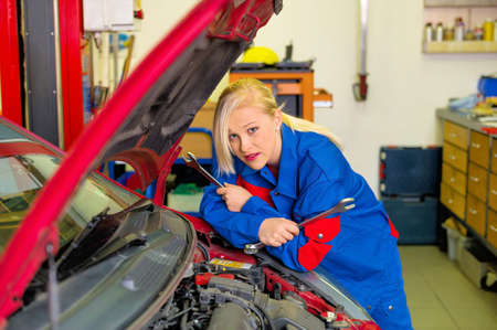 repaired: a young woman as a mechanic in a garage. rare professions for women. car will be repaired in the workshop
