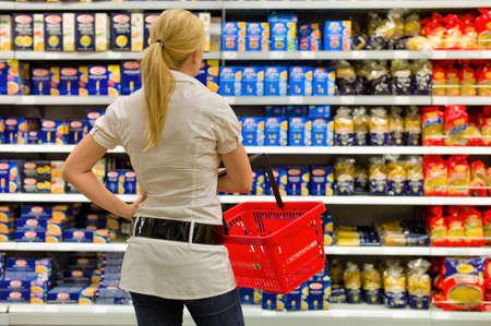 een vrouw wordt overweldigd door de grote selectie in een supermarkt bij het winkelen. Stockfoto