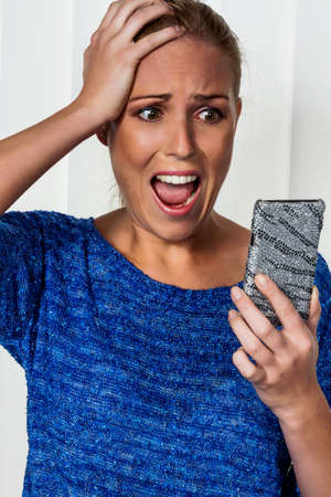 horrified: a woman gets bad news via sms and is shocked. Stock Photo