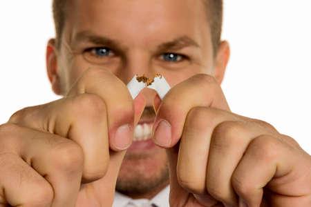 un homme veut arrêter de fumer et brise sa dernière cigarette