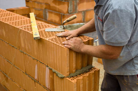 single familiy: trabajador de la construcci�n en el anonimato en una obra en construcci�n de viviendas erigi� una pared de ladrillos. pared de ladrillos de una casa. imagen de icono para el trabajo no declarado y la chapuza