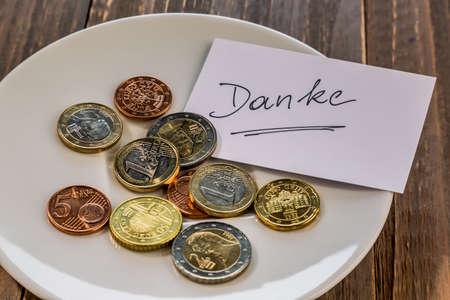 sacrificio: un plato de monedas por consejo o cuota para inodoros. en idioma alemán Foto de archivo