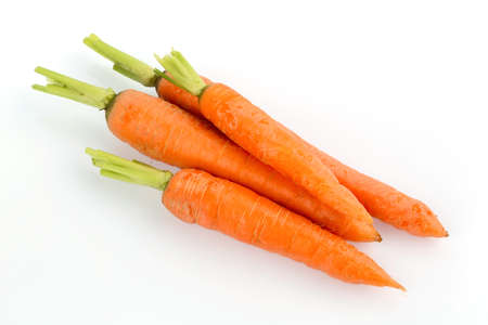 organically: organically grown carrots lying on white background. fresh fruit and vegetables is always healthy.