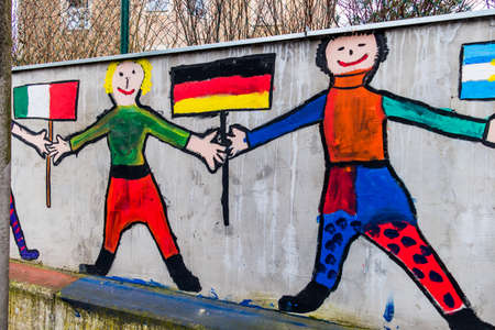 migration: on the wall of a school children have students painted. symbolic photo for coexistence and migration